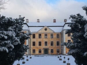 Christinehof om vintern. Snön ligger tung på idegranarna som omgärdar infarten. Mer om idegran, se skylt 15